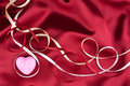 Pink heart and satin ribbons lie on red background Royalty Free Stock Photo
