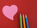 Pink heart shaped memorandum on red paper with colorful pencils remember meaning of love Royalty Free Stock Photography