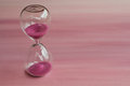 Pink hourglass closeup on background Royalty Free Stock Photos