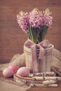 Pink hyacinths and easter eggs in a wooden flower pot Royalty Free Stock Image