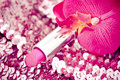 Pink lipstick on glitters with orchid Stock Photos