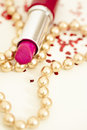 Pink lipstick with golden beaded necklace Stock Images