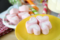 Pink marshmallow yellow plate Stock Photos