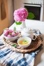 Pink marshmallows, mug of mint herbal tea, white teapot and hydrangea flowers on kitchen table. Royalty Free Stock Photo