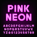 Pink neon tube alphabet font. Type letters and numbers on a dark background.