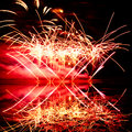 Pink and orange fireworks reflected in a murky lake Royalty Free Stock Photos