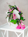 Pink orchid wreath and kid s shoes still life with hanging on the retro style photo frame infant standing on white wooden stand Stock Photography