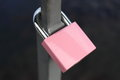 Pink padlock attached to a rail Royalty Free Stock Photo