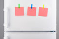 Pink paper notes attached with stickers on white refrigerator Royalty Free Stock Photo