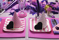 Pink party hats on table setting and purple theme decorations with stripe square plates polka dot and strip heart Royalty Free Stock Photo