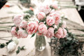 Pink peonies in vase on wooden floor and bokeh background - retro styled photo. soft focus. Royalty Free Stock Photo