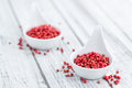 Pink Peppercorns on wooden background; selective focus