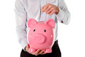 Pink piggy bank with businessman in the background close up of a giant a business man dropping a coin int it wear a blue shirt and Stock Images
