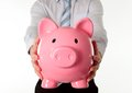 Pink piggy bank with businessman in the background close up of a giant a business man wear a blue shirt and blue tie on a white Royalty Free Stock Image