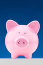 Pink piggy bank front view of a ceramic on a blue background Royalty Free Stock Photography
