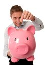 Pink piggy bank with man inserting coins into it close up a businessman a coin wearing a blue shirt on a white background Stock Images