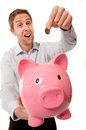 Pink piggy bank with man inserting coins into it close up a happy smiling businessman a coin wearing a blue shirt on a white Stock Photo
