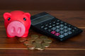 Pink piggy bank sitting on pile of coins next to calculator Royalty Free Stock Photo