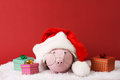 Pink piggy box wiht glasses and santa hat with pompom and three gift boxes with ribbon standing on white snow on red background Royalty Free Stock Photo