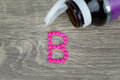 Pink pills forming shape to B alphabet on wood background Royalty Free Stock Photo
