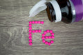 Pink pills forming shape to Fe alphabet on wood background