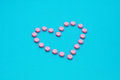 Pink Pills In Heart Shape  on Blue background Royalty Free Stock Photo
