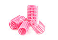 Pink plastic hair curler against white background Stock Image