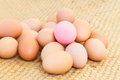 Pink preserved egg on fresh eggs Royalty Free Stock Photo