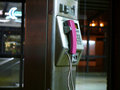Pink public telephone in nightly subway station Stock Photos