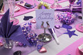 Pink and purple birthday party table setting theme decorations with happy message on stand Stock Photos