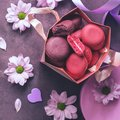 Pink and purple macaroon close-up in a gift paper bag on a purple background decorated with flowers. Top view, selective focus. Royalty Free Stock Photo