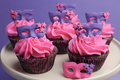 Pink and purple masquerade masks decorated party c cupcakes with frosting for teenage birthday new years eve or wedding bridal Stock Photography
