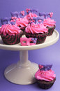 Pink and purple masquerade masks decorated party cupcakes with frosting for teenage birthday new years eve or wedding bridal Stock Photo
