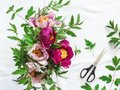 stock image of  Pink and purple peonies in a vase on a white table