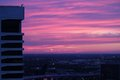 Pink and purple sunset sky high rise building in the shadow of a brilliant the tower mirrors the lines of the horizon bridge cloud Royalty Free Stock Photos