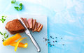 Pink roasted duck breast cut in fillets with ingredients on a cutting board Stock Images