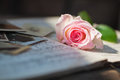 Pink rose and antique photos lying on sheets of music Royalty Free Stock Photos