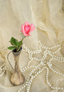 Pink rose in an antique silver vase with pearls on beige cloth Stock Photos
