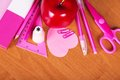 Pink school accessories set of bright office tools and red apple on a table Royalty Free Stock Image