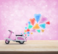 Pink scooter toy with colorful heart love balloon on wooden tabl Royalty Free Stock Photo