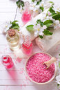 Pink sea salt in bowl, bottles with aroma oil, towels  and flowe Royalty Free Stock Photo