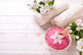 Pink sea salt in bowl, towels  and flowers on white wooden backg Royalty Free Stock Photo