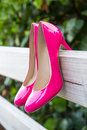 Pink shoes on fence pair of hanging wooden outdoors Royalty Free Stock Image