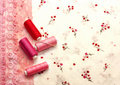 Pink spools of thread on a floral fabric Stock Photography