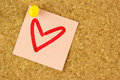Pink sticker with draw heart on the corkboard paper pined closeup Royalty Free Stock Images