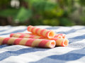 Pink striped wafer rolls on blue plaid tablecloth. The background is green from tree and light bokeh Royalty Free Stock Photo
