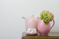 Pink teapot and marshmallows jar with hydrangea in it on a wooden table in the living room Royalty Free Stock Images