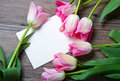 Pink tulips and card bouquet of postcard on wood Stock Photo