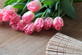 Pink tulips with fan on wooden board Royalty Free Stock Photo
