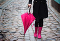 Pink umbrella and pink rubber boots woman with walking down the street holding Royalty Free Stock Image